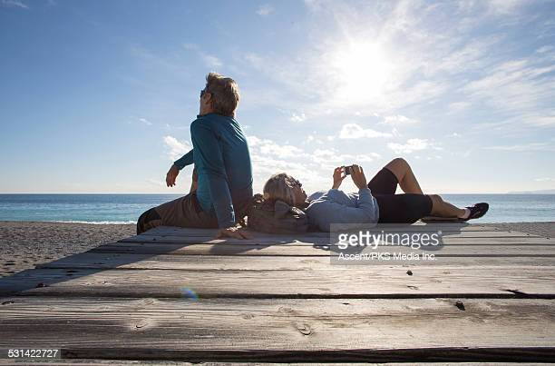Couple relax on beach wharf, woman sends text