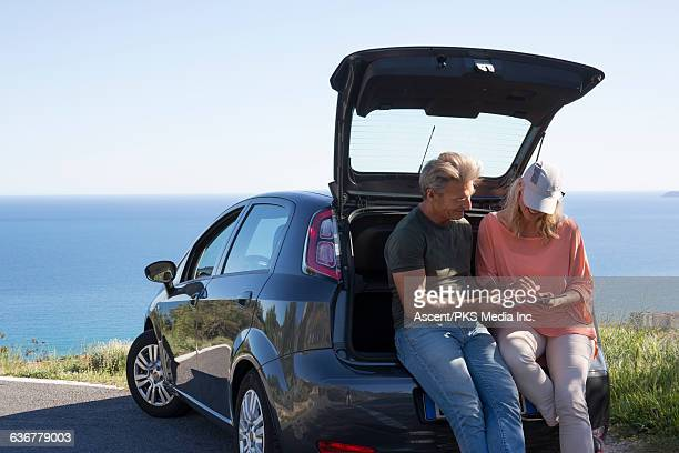 Couple relax on car tailgate, look at tablet, sea