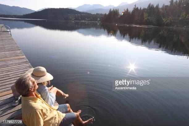 カップルは日の出時に湖畔の桟橋でリラックス - ウォーターフロント ストックフォトと画像