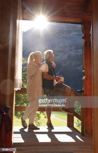 Couple relax on mountain chalet veranda