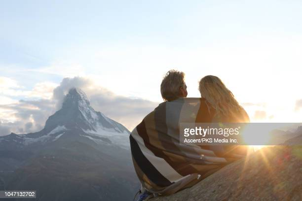 couple relax on rock ledge, nestle into blanket - schöne natur stock-fotos und bilder