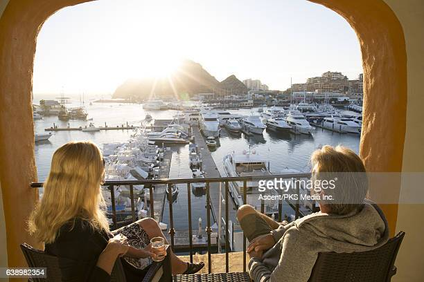 Couple relax on terrace above marina