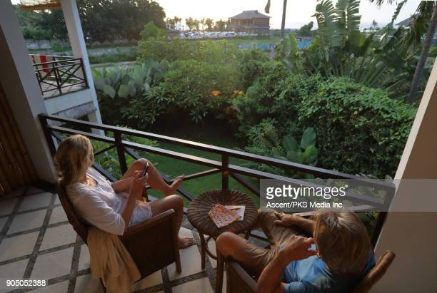 Couple relax on terrace of tropical villa, sunrise
