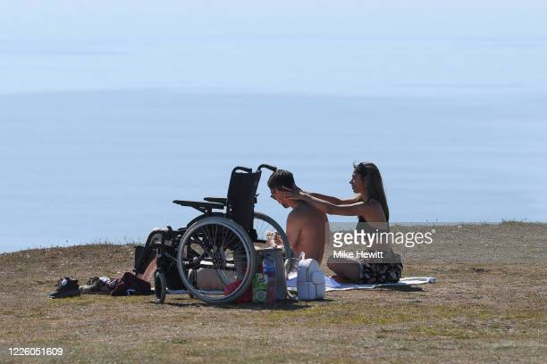 Couple relax on the cliff tops near Belle Tout lighthouse on May 20, 2020 near Eastbourne, England. Parts of the country were expected to reach 29...
