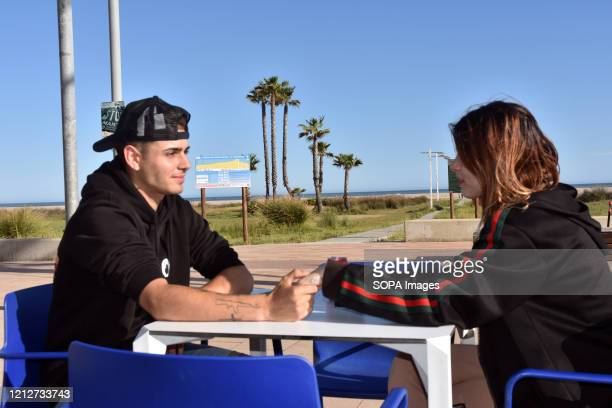 A couple relax on the terrace of a beachside restaurant amid coronavirus crisis Having managed to pass to Phase 1 the bars and restaurants of El...