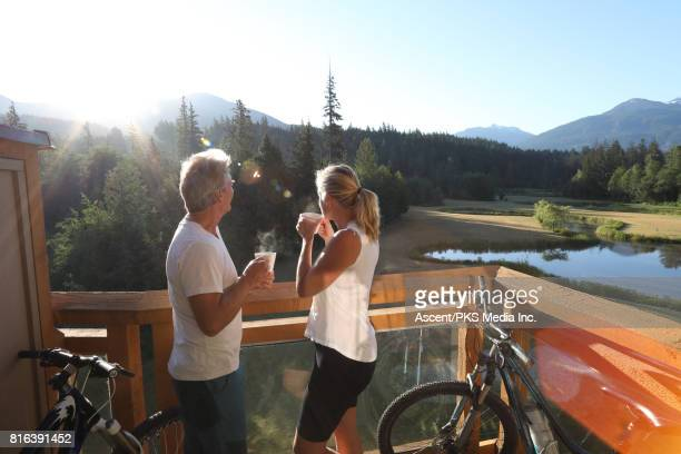 Couple relax on veranda with bikes, hot drinks