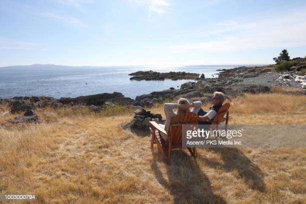 couple relax on wooden chair, look out to calm sea - victoria canada stock pictures, royalty-free photos & images