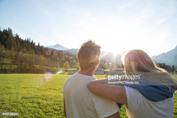 Couple relax together in mountain meadow, sunrise