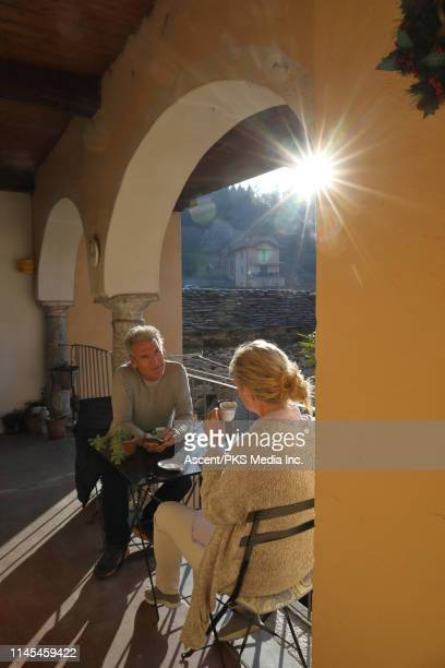 couple relax under portico, look at smart phone - mature couple stock pictures, royalty-free photos & images