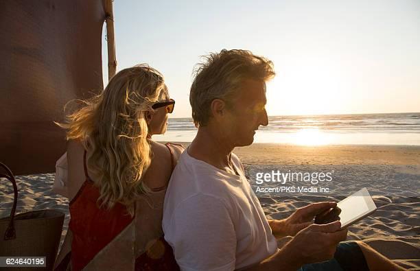 Couple relax & use digital tablet, on beach