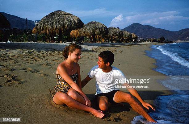 A couple relaxes on the beach in Acapulco Mexico