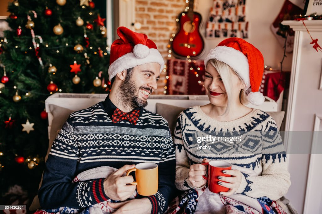 Couple relaxing and drinking tea in front of a Christmas tree : Stock Photo