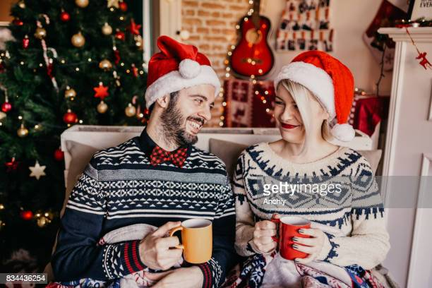 Couple relaxing and drinking tea in front of a Christmas tree