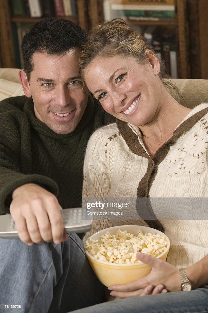 Couple relaxing and eating popcorn : Stockfoto