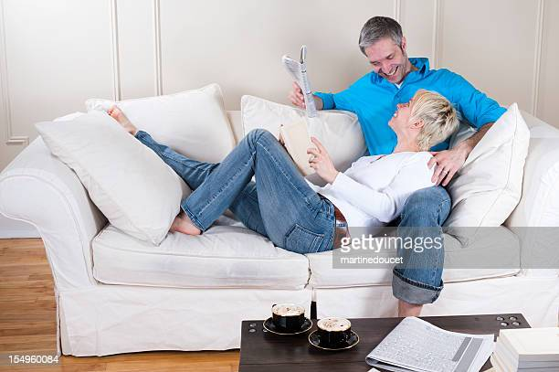 Couple relaxing and reading on a couch.