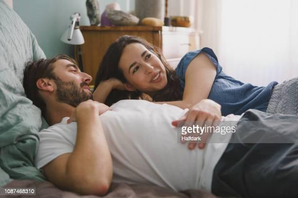 couple relaxing and talking on bed - mid volwassen stockfoto's en -beelden