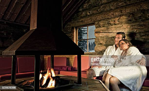 Couple relaxing at fireplace in log cabin