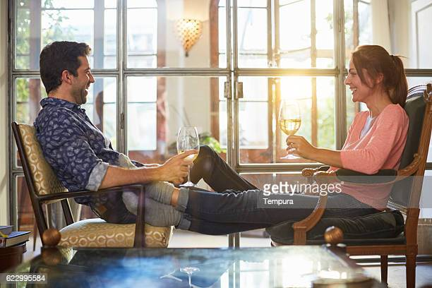 Couple relaxing at home and sharing a cup of wine