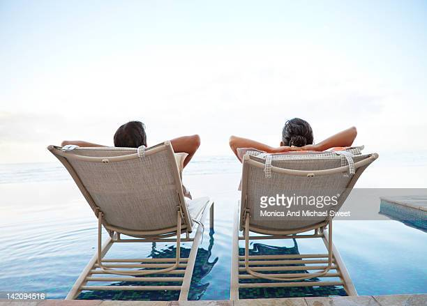 Couple relaxing at infinity pool