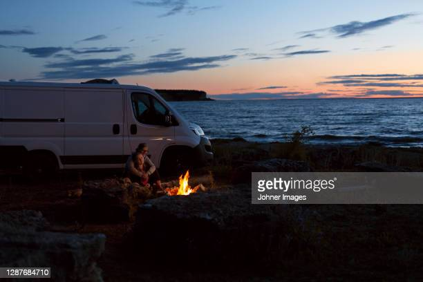 couple relaxing at log fire by sea - sweden stock pictures, royalty-free photos & images