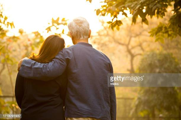 couple relaxing at park - arm around stock pictures, royalty-free photos & images