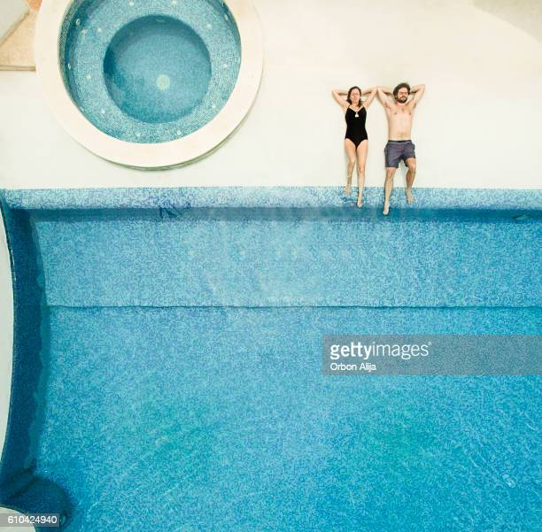 Couple relaxing at swimming pool