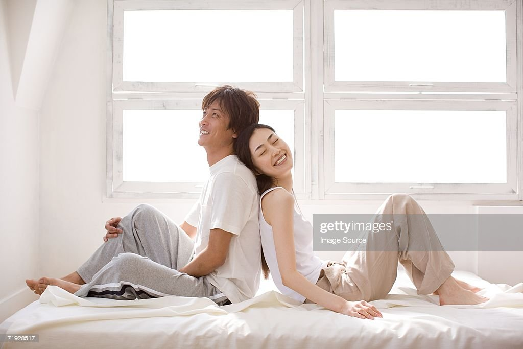 Couple relaxing back to back : Stock Photo