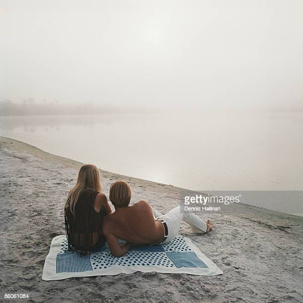Couple relaxing by misty lakeside at sunrise