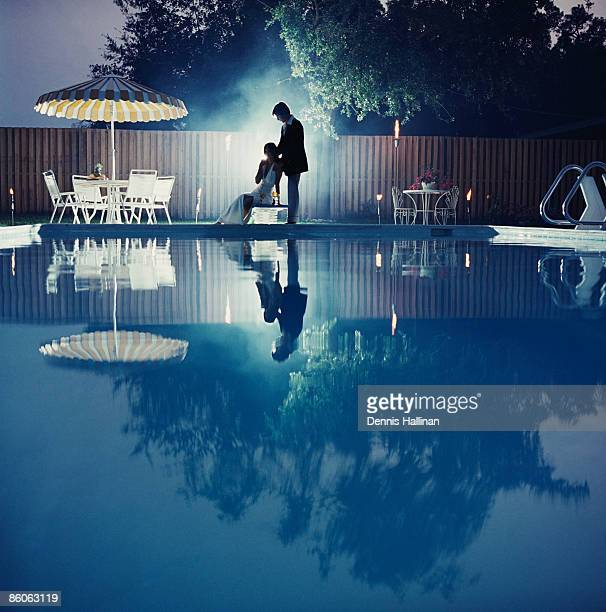 Couple relaxing by swimming pool at night