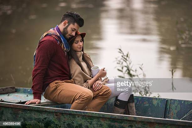 Couple relaxing in a boat with their eyes closed.