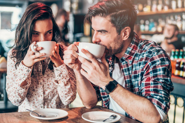 couple relaxing in a cafe - couples romance stock pictures, royalty-free photos & images