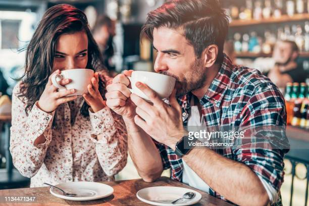 couple relaxing in a cafe - flirting stock pictures, royalty-free photos & images