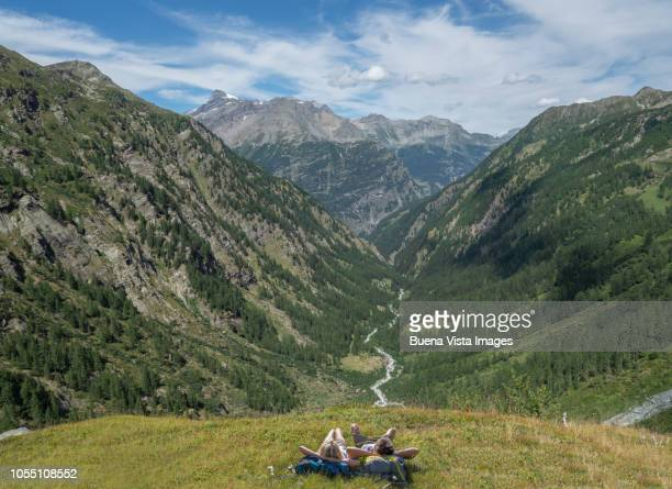 couple relaxing in a meadow - monte rosa foto e immagini stock