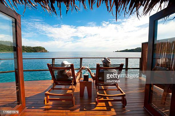 couple relaxing in an over water bungalow - fiji stock pictures, royalty-free photos & images