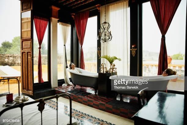 Couple relaxing in bathtubs in bedroom in boutique hotel
