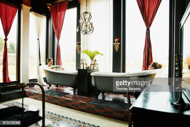 Couple relaxing in bathtubs in bedroom of boutique hotel