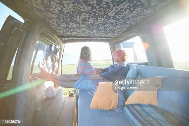 couple relaxing in camper van on atlantic coastline. - dougal waters stock pictures, royalty-free photos & images