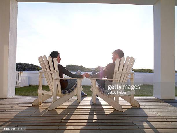 Couple relaxing in chairs on veranda, holding hands, rear view