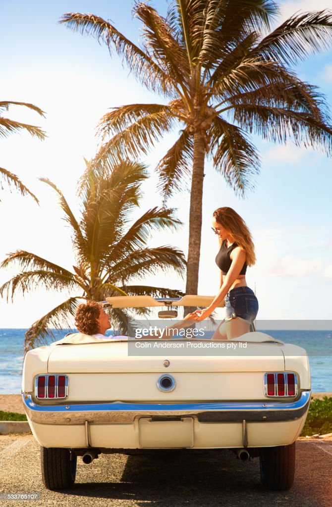 Couple relaxing in convertible on beach : Foto stock