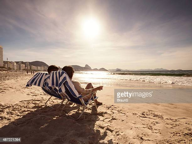 Couple relaxing in deck chairs on the beach at sunset.