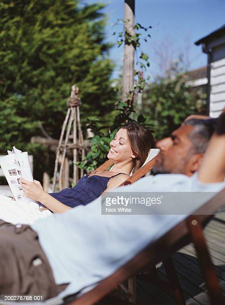 couple relaxing in deckchairs, woman reading magazine, smiling - picture magazine stock photos and pictures
