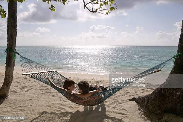 Couple relaxing in hammock on tropical beach, dawn, rear view