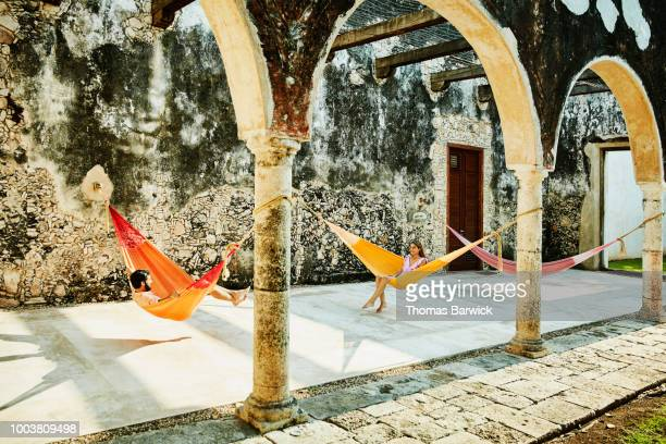 Couple relaxing in hammocks at luxury resort