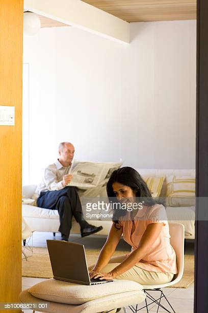 Couple relaxing in living room, woman using laptop
