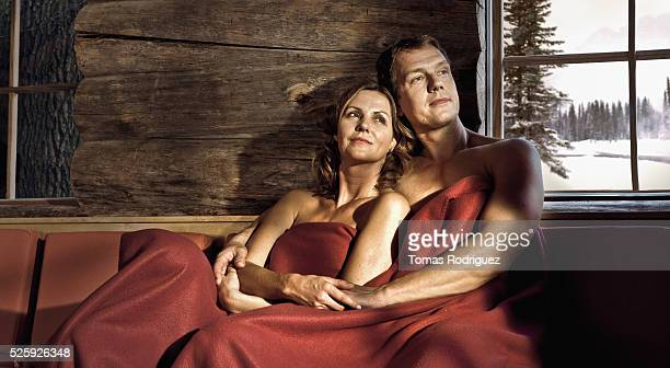 Couple relaxing in log cabin