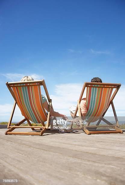Ein paar Entspannung in Liegestühlen Hände halten