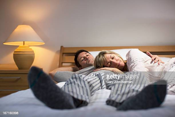 Couple relaxing in pyjamas at home