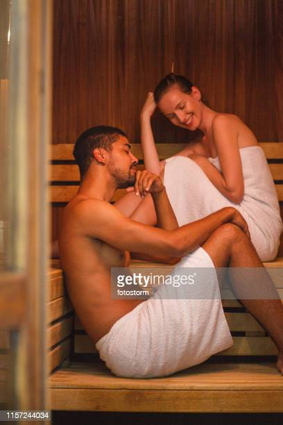 couple relaxing in sauna - wrapped in a towel stock pictures, royalty-free photos & images