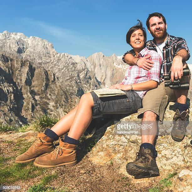 Casal relaxante no sentada no topo da montanha