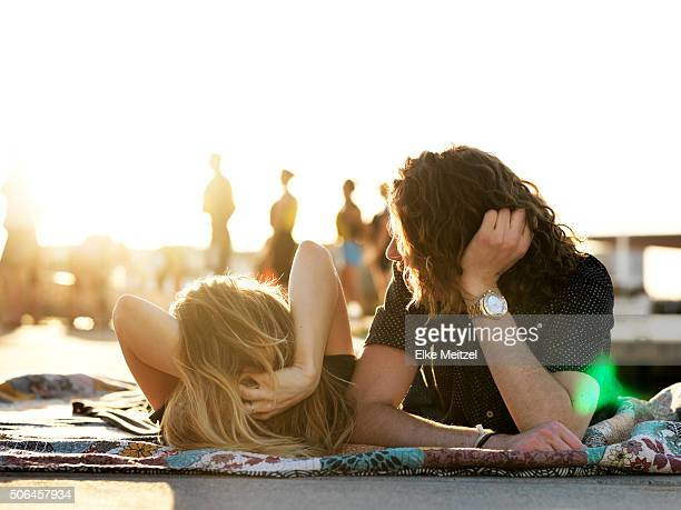 couple relaxing in the sunshine watching people passing by